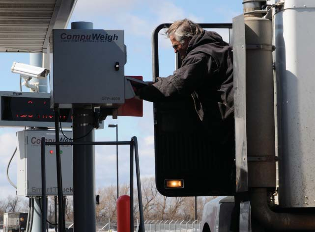 Trucker receives a scale ticket from a printer adjacent to the outbound scale, all part of a CompuWeigh SmartTruck traffi c management system at Hankinson Renewable Energy's ethanol plant at Hankinson, ND. Photos by Rob Siverson, Fargo, ND.
