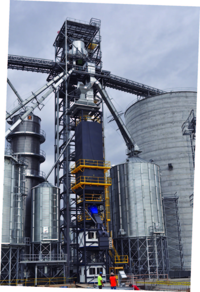 Grain handling equipment from left includes a Zimmerman 4,750-bph tower dryer, Chief screenings tanks, two Schlagel 30,000-bph receiving legs enclosed in an Allstate support tower, Schlagel rotary double distributor, InterSystems gravity screener, and 60,000-bph CompuWeigh bulk weigh loadout scale.